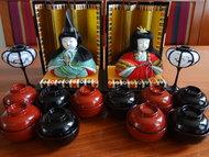 Hina Doll set Hokkaido Japanse Poppen Japan Vintage  Elk jaar op 3 maart wordt de Hina Matsuri, ook wel Doll Festival gevierd. Op deze dag wensen families met meisjes hun dochters een succesvol en gelukkig leven. Op verschillende platforms worden poppen neergezet, met bovenaan voor een gouden achtergrond de keizer en keizerin. Dit festival vindt zijn oorsprong in een Chinese gewoonte waarbij ongeluk overgedragen wordt aan poppen. De poppen die hiervoor gebruikt worden zijn vaak al heel oud, overgegeven van generatie op generatie. Het eten dat geofferd wordt aan de poppen bestaat onder andere uit diamantvormige rijstwafels, hartvormig snoep en er wordt zoete sake gedronken.  Veel mensen zetten kleine platforms neer bij gebrek aan ruimte